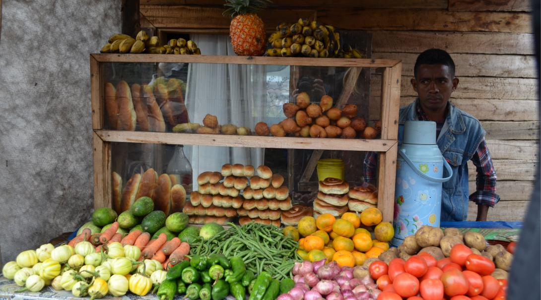 A local store keeper in Madagascar selling naturally grown fruits, vegetables, and vegan breads